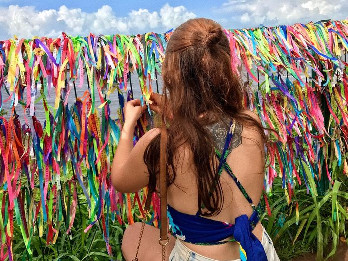 Woman tying ribbon on railing in city