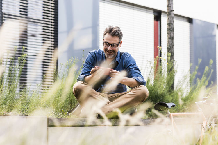 Young man sitting against plants