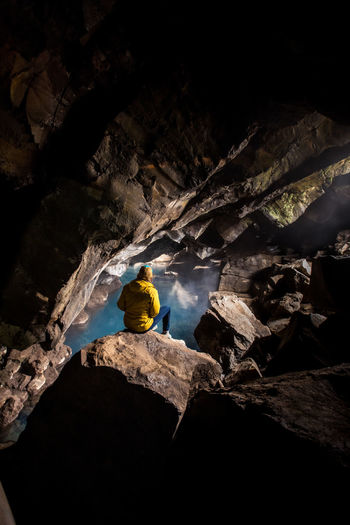 Rear view of man on rock in cave