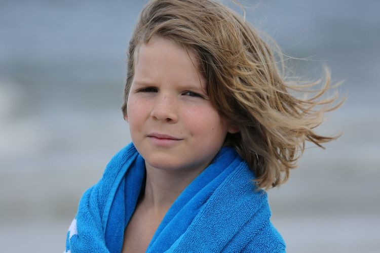 Portrait Of Boy With Long Hair Wrapped In Blue Towel