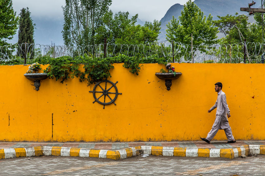 Man Walking Wall - Building Feature Yellow Color Plant Green Color Outdoors Street Photography Travel Destinations Travel Traveling Travel Photography Pakistan Footpath National Dress City
