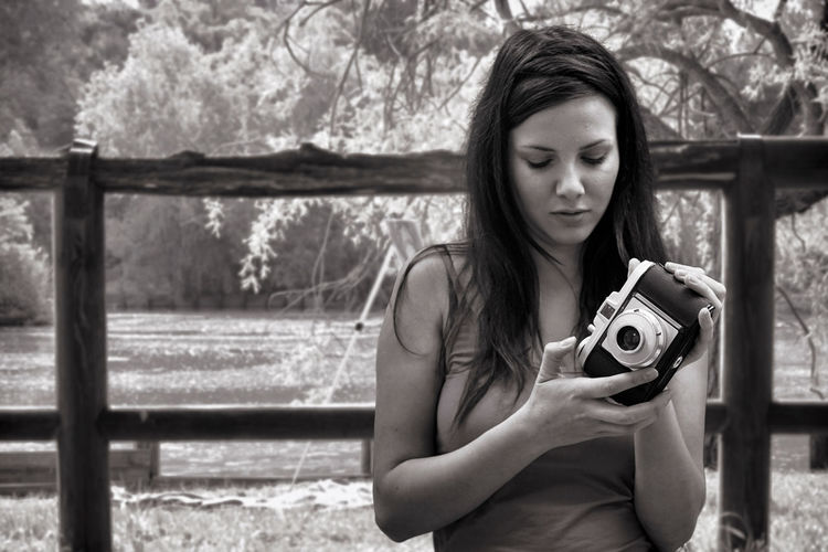 Young Woman Holding Camera While Standing At Public Park