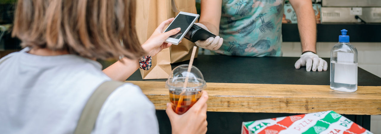 Woman making contactless payment through smart phone at restaurant