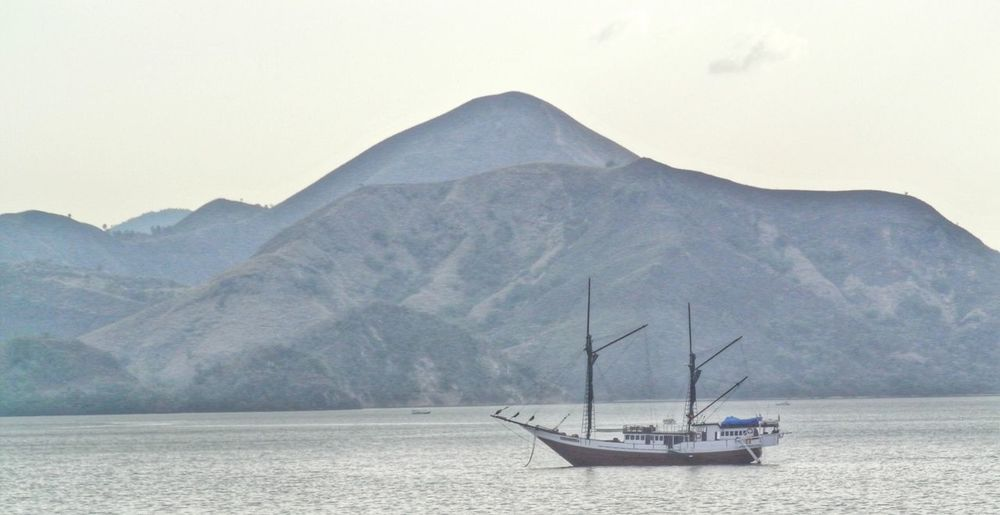 Boat Sailing On Sea By Mountain Against Clear Sky
