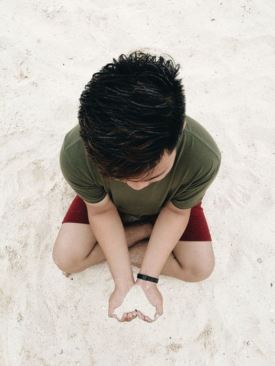 High Angle View Of Man Holding Sand In Heart Shape While Sitting At Beach