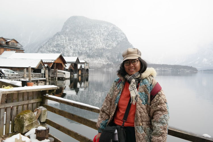 Portrait Of Smiling Woman Wearing Warm Clothing While Standing Against River During Winter