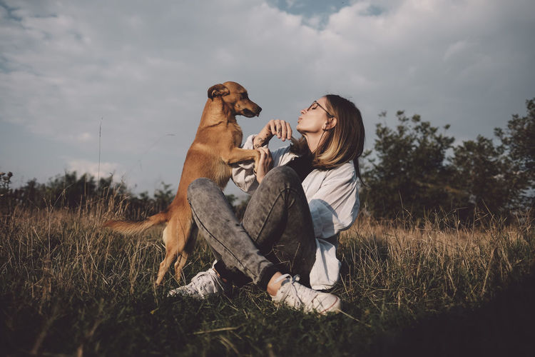Young woman playing with dog on grass against sky