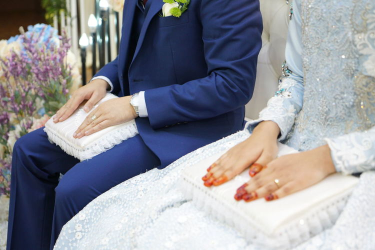 Midsection Of Bride And Groom Sitting During Wedding Ceremony