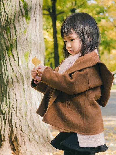 Side View Of Girl Holding Yellow Leaf While Standing By Tree Trunk