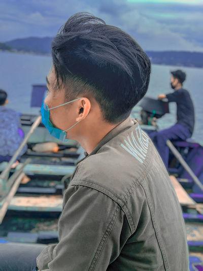Rear view of boy sitting on boat