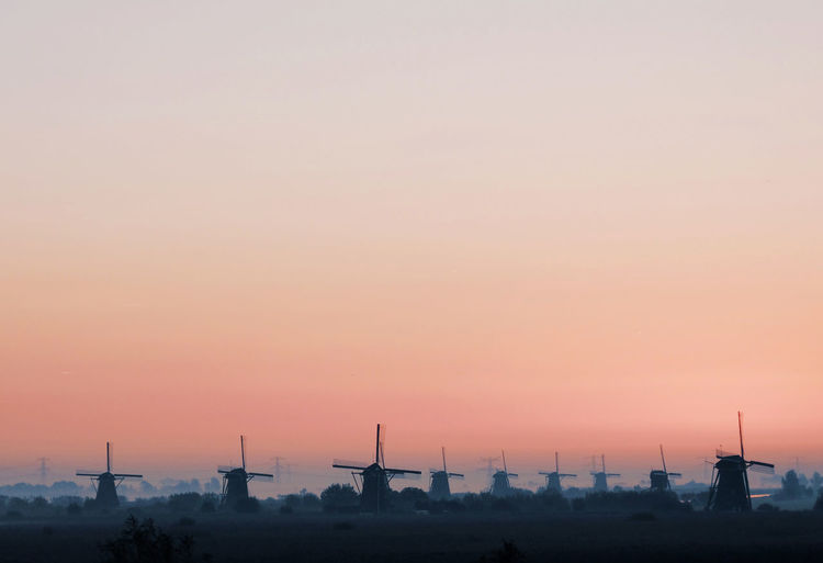 Traditional Windmills Against Clear Sky During Sunset