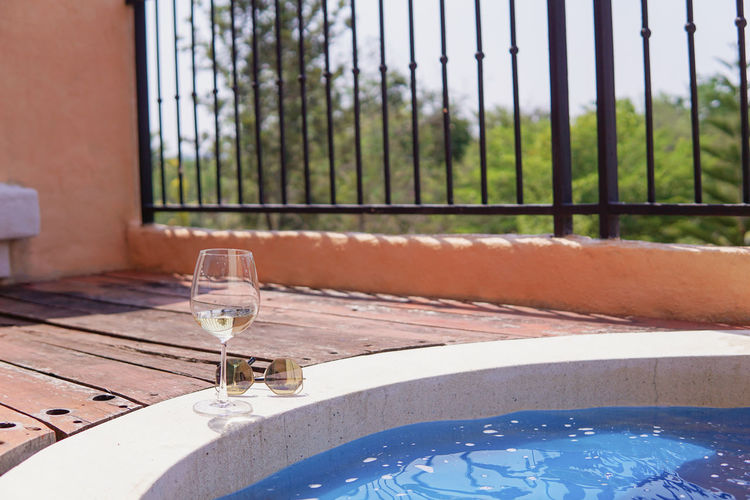 Close-up of wine glass on table by swimming pool