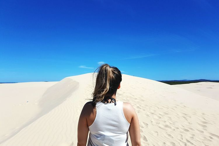 Rear view of woman standing on sand dune against blue sky