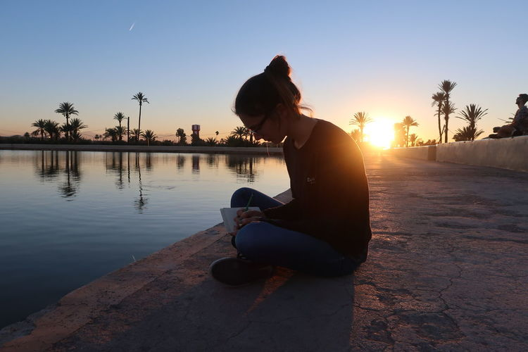 Full length of woman writing on diary while sitting by lake