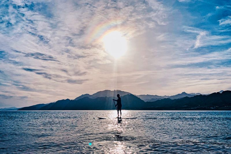 Silhouette person paddleboarding on sea against sky