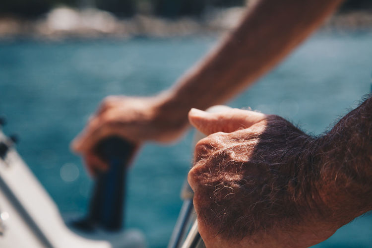 Cropped hands of man riding motorboat on sea