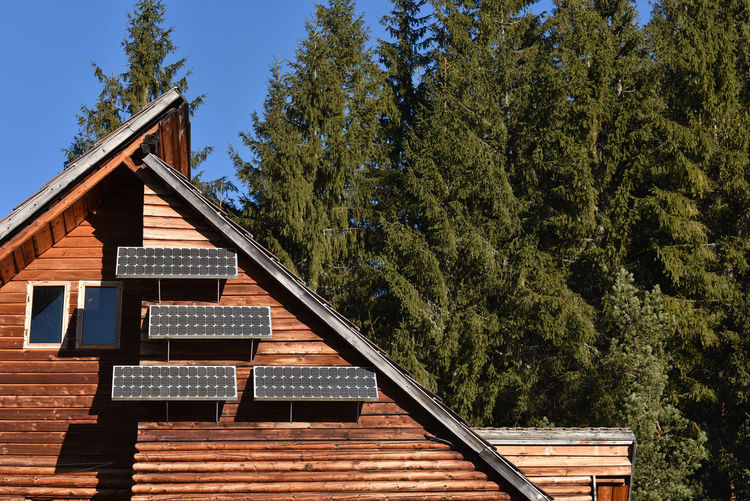 Low Angle View Of Wooden House With Solar Panels Amidst Trees Against Sky