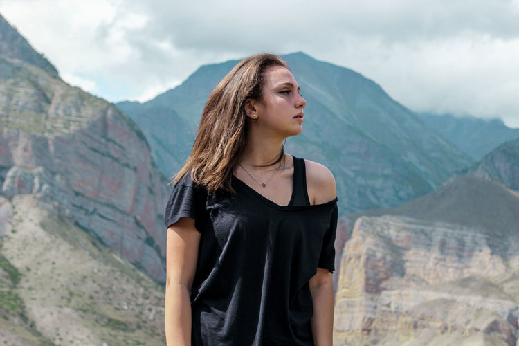 Beautiful young woman looking away while standing against mountain range