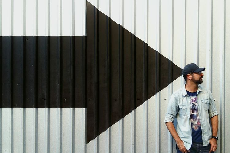 Man standing by arrow symbol on corrugated iron