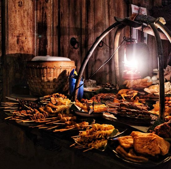 Barbecued food displayed at market stall during night