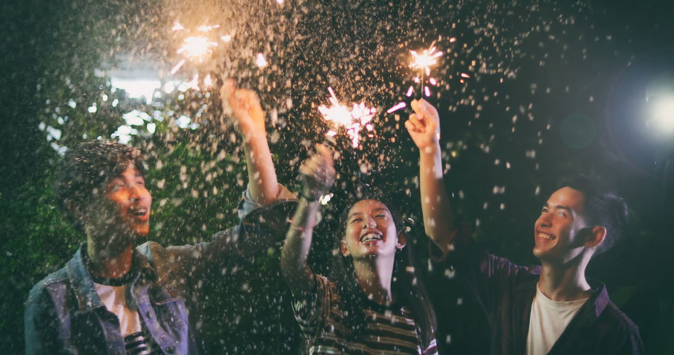 Group of happy friends with illuminated sparklers and drink enjoying at backyard during night