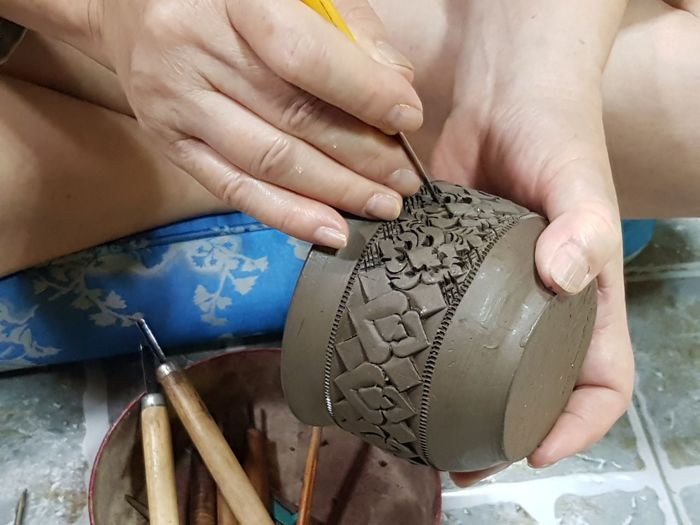 Close-up of person carving on earthenware