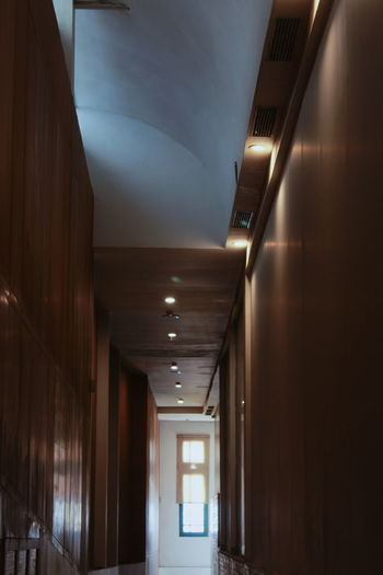 Low angle view of illuminated corridor of building