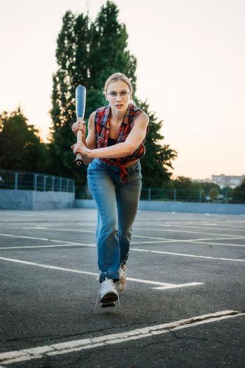 Girl power, feminism, women self-defense. portrait of woman with baseball bat on parking outdoor