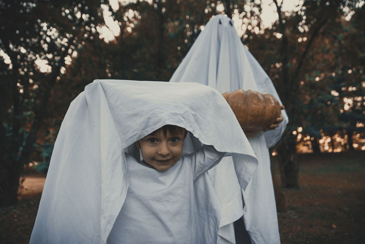 Portrait of cute boy with person wearing ghost costume in park at sunset during halloween