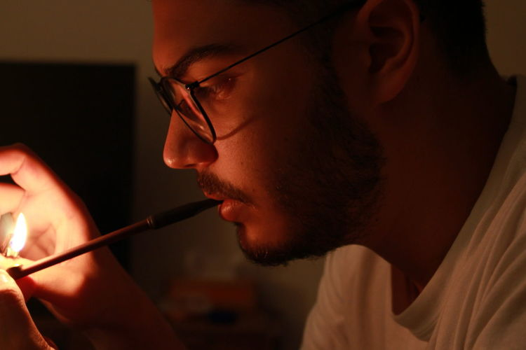 Close-up of young man igniting tobacco product