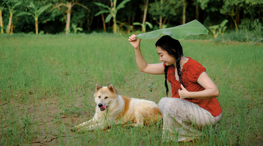 Full length of a girl with dog on the field