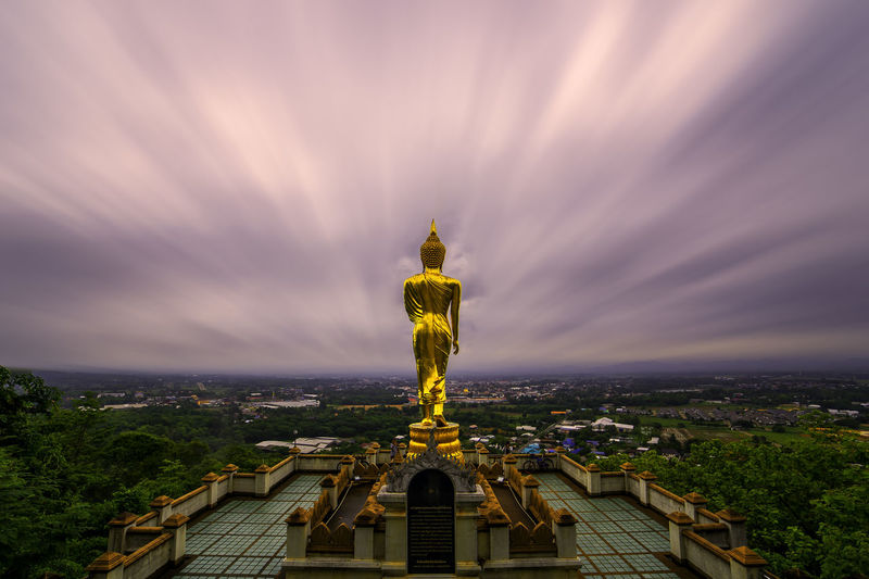 Buddha statue against cloudy sky during sunset