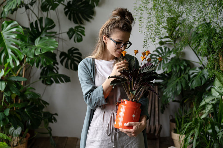 Young woman holding plant while standing against potted plants
