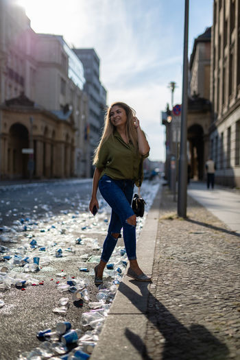 Full length portrait of woman on footpath in city