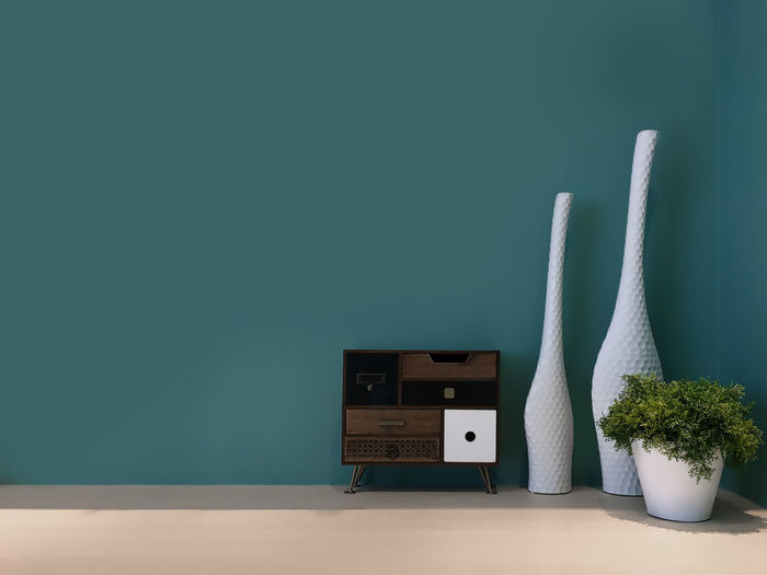 Vases By Sideboard Against Blue Wall At Home