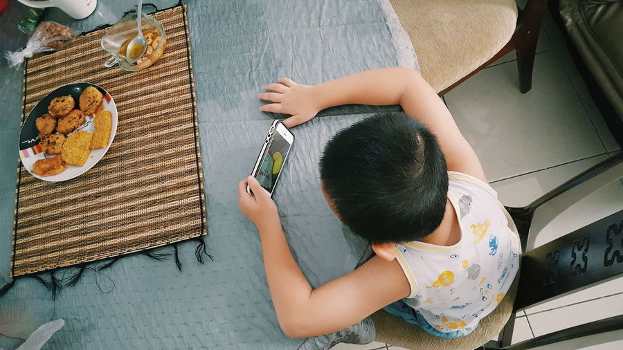 High angle view of boy using a smart phone