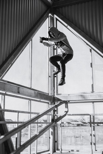 Full length of man jumping against fence