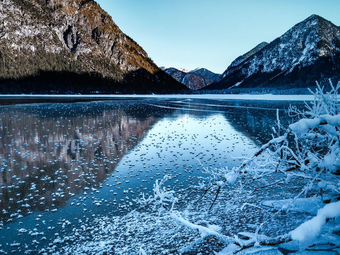 Ice crystals on a frozen lake at heiterwang, tyrol, austria against mountains