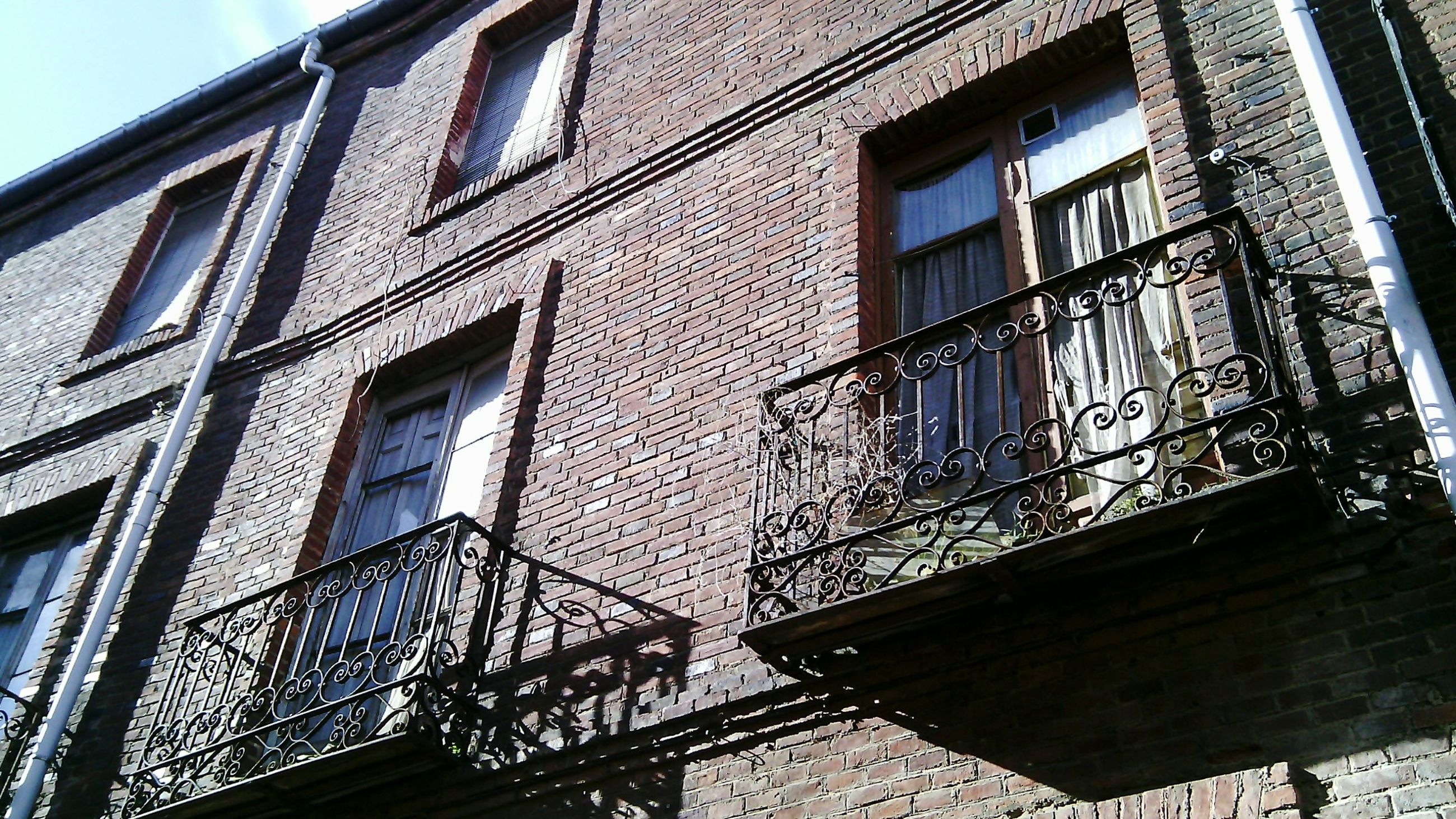 architecture, building exterior, built structure, window, low angle view, building, residential building, residential structure, brick wall, city, glass - material, day, outdoors, no people, balcony, apartment, reflection, facade, sky, house