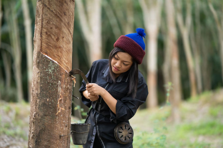Young woman working by tree during winter