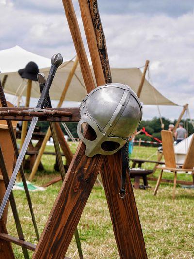 Reenactment helmet and sword on wooden structure