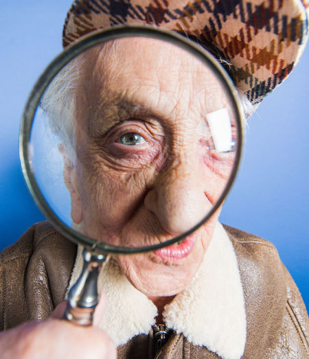 Portrait of senior woman looking through magnifying glass against blue background