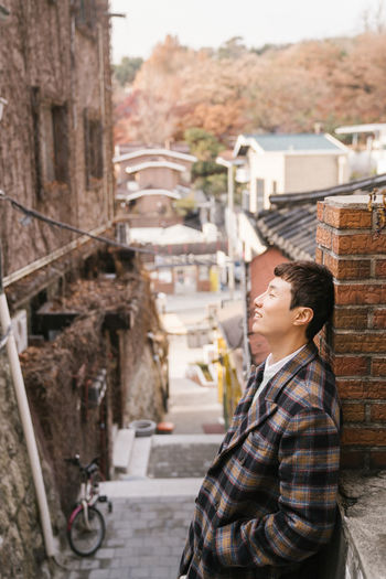 Side view of boy standing against buildings in city