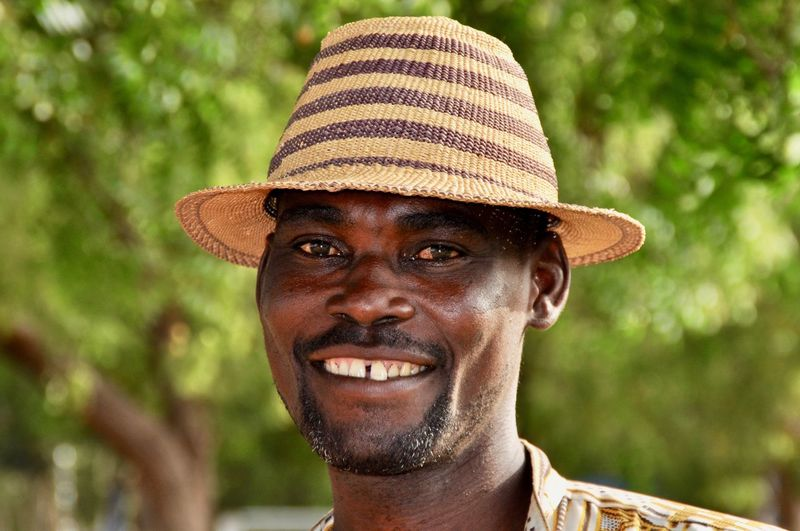 Developing Country Portrait One Person Hat Men Adult Africa Faces Of Africa African Ghana Market Vendor Cheerfully Straw Hat Headshot Smiling Looking At Camera Happiness Emotion Teeth Facial Hair Human Face Body Part Toothy Smile Focus On Foreground Close-up Hat Looking At Camera Adult Males  Beard