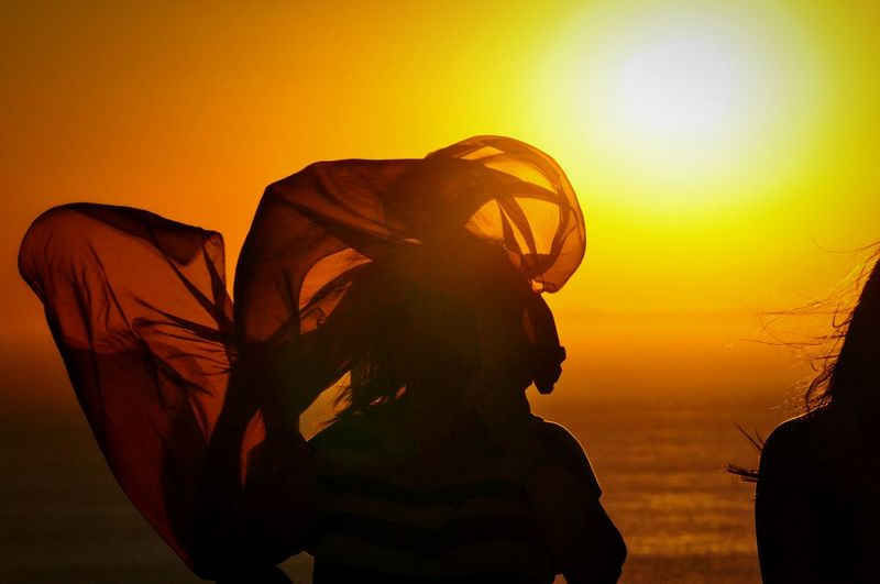 Woman Silhouette Waving Fabric Against Sea During Sunset