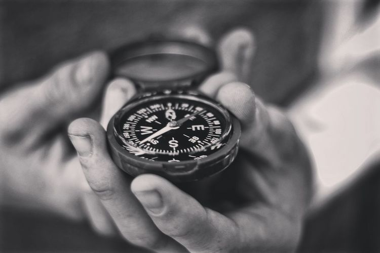 Close-Up Of Person Hand Holding Navigational Compass