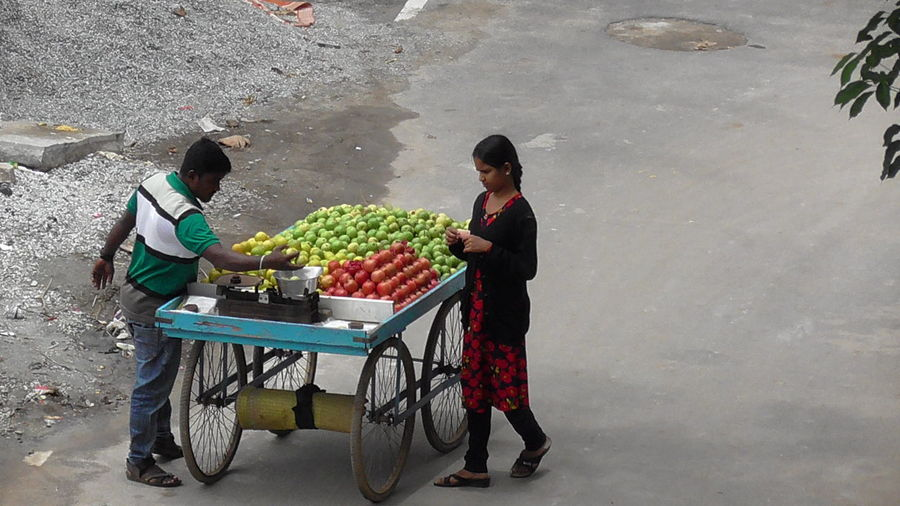 High angle view of woman buying fruits from street vendor