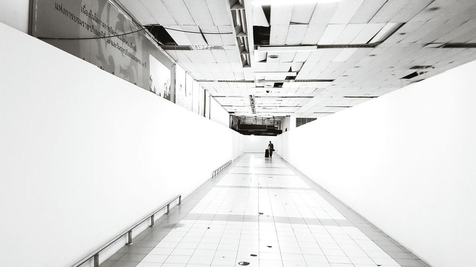 Walking The Way Forward Built Structure Architecture Full Length City Indoors  People One Person Day One Man Only Monochrome Black And White Photography Blackandwhite Black And White Vanishing Point Pathway To Heaven Perspective Path To Nowhere Travel Traveling Journey On The Way On The Move On The Go  The City Light