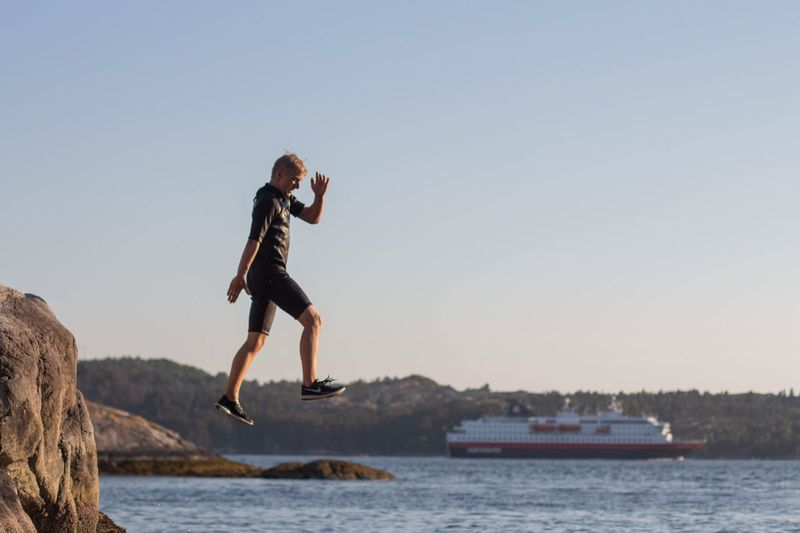 Side view of man jumping on rock against sky