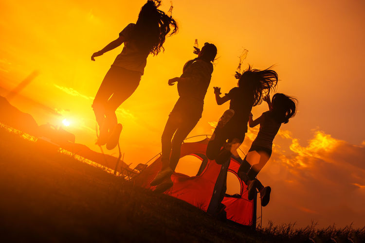 Silhouette Group of women party with drink bottles and jumping enjoy travel camping,trekking in vacation time at sunset. Sunset Sky Orange Color Group Of People Sport Nature Leisure Activity Silhouette Lifestyles Real People Men Full Length Helmet Sunlight People Activity Headwear Sun Extreme Sports Adventure Outdoors Riding